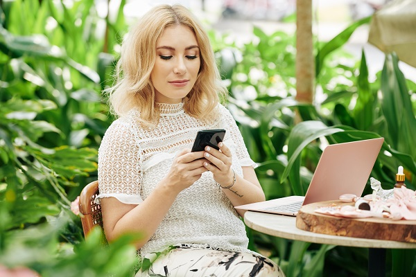 Blond charming Icelandic woman sitting using her smartphone and laptop