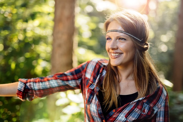 Beautiful smiling Norwegian woman posing all alone standing in a green forest