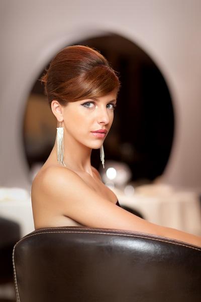 Elegant serious French girls wearing stunning earrings posing for the camera sitting still