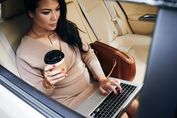 Young charming serious Thai woman sitting in her car with a cup of coffee working alone