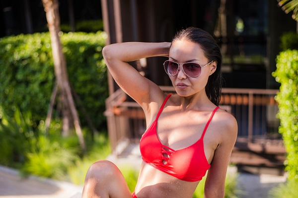 Attractive curvy Thai woman sunbathing in a bikini at the tropical travel resort