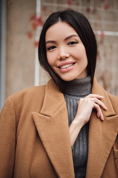 Portrait of a gorgeous Japanese girl in a brown coat happily looking in a camera outdoors