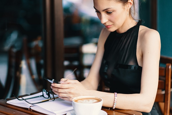 Beautiful Icelandic business lady drinking a cup of coffee and uses her phone