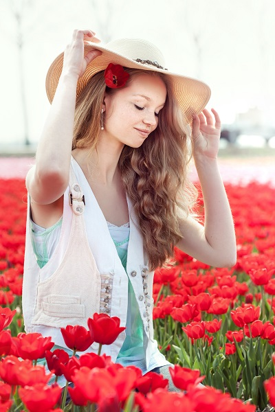 Beautiful smiling Dutch woman sitting on a field of red tulips touching the hat with her fingers