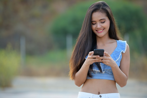 Young happy beautiful Thai woman using her phone chatting with her boyfriend