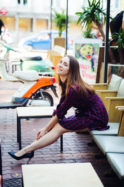 Smiling attractive Spanish female wearing a checkered dress sitting on a chair
