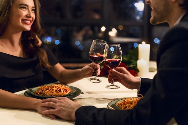 Smiling charming Spanish woman drinking a glass of red wine with her boyfriend