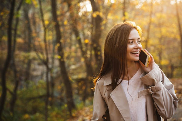 Image of a young Ukrainian woman using her smartphone while walking in an autumn park