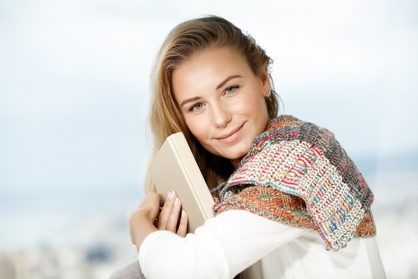 Young beautiful Belarusian girl sitting with a book in her hands