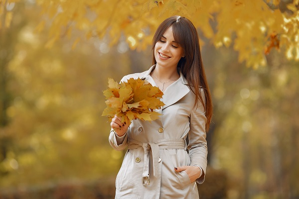 Charming beautiful Lithuanian woman walking with a bouquet of yellow leaves all alone