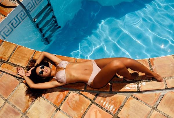 Young beautiful Egyptian girls lying near a swimming pool sunbathing