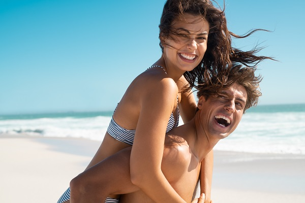 Laughing Puerto Rican lady with her boyfriend on a sandy beach