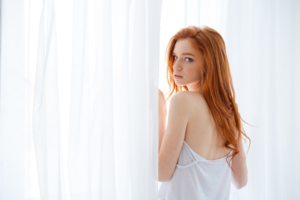 Red-haired Irish woman standing near the window with a white curtain
