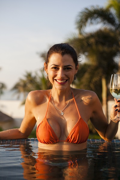 Smiling adult Puerto Rican lady sitting in a swimming pool with a glass of wine