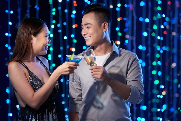 Smiling attractive South Korean woman drinking a cocktail with her boyfriend