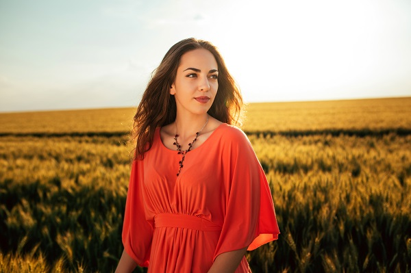 Attractive smiling Greek woman standing in a wheat field all by herself