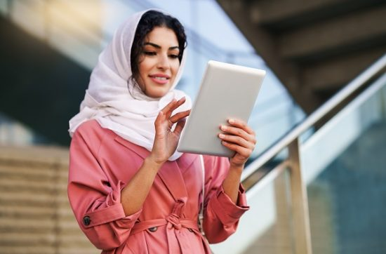 Beautiful Syrian girl using her tablet to chat online