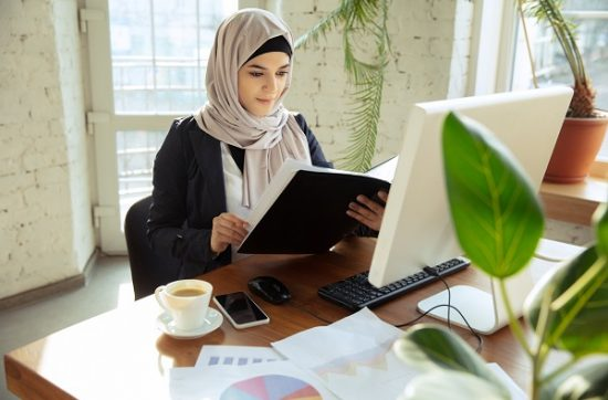 Young Yemeni girl sitting at the computer alone
