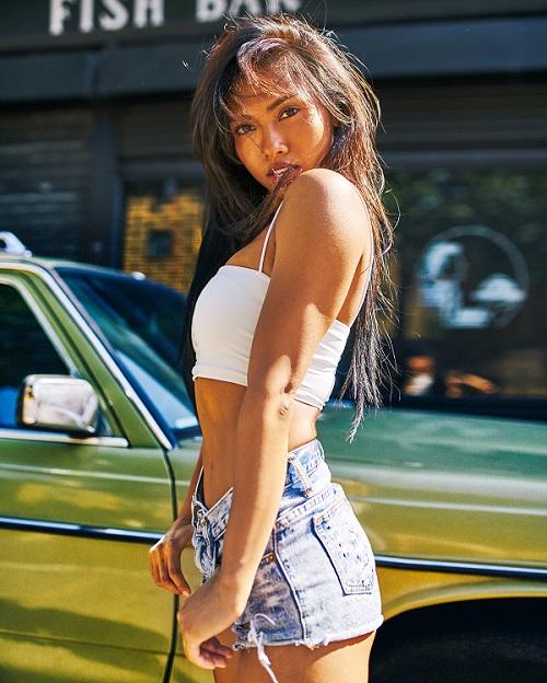 Sexy curvy Cambodian girl posing in jean shorts near a car