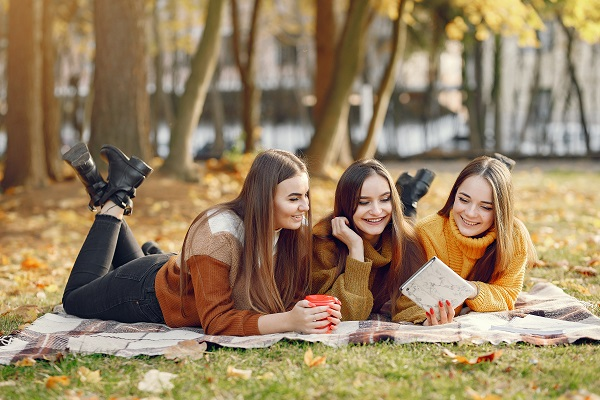 Three young attractive Lithuanian girls lying on a blanket during an autumn day