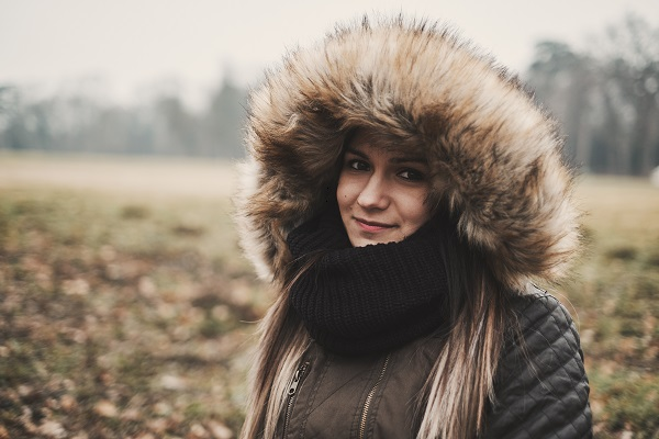 Winter portrait of a young smiling Serbian woman posing for the camera in a field