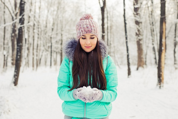 Young smiling brunette Swedish woman standing in a winter forest playing with snow