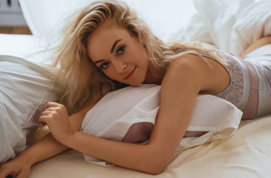 Smiling blond-haired Latvian girl lying in her bad together with a pillow