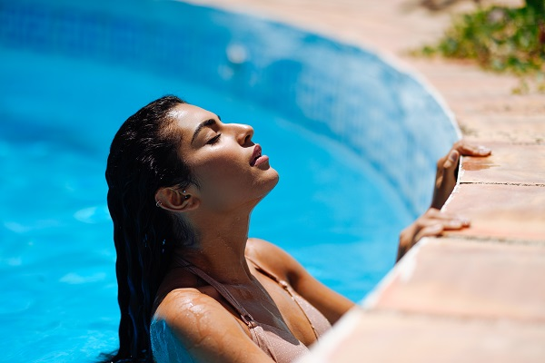 Beautiful sexy Turkish girl relaxing in a swimming pool with her eyes closed
