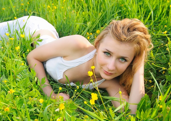 Charming Latvian woman lying in green grass in a field during the summer