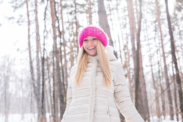 Young pretty Swedish woman throwing snow in the air during her winter holidays