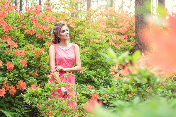 Curvy blonde Greek woman wearing a pink dress standing in a green garden full of flowers