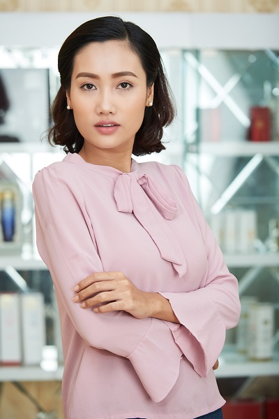 Beautiful South Korean woman posing for a photo wearing a pink blouse