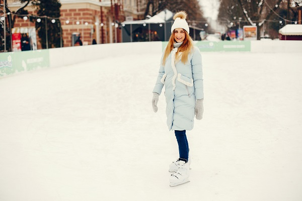 Young blonde Serbian woman spending her free time on a skating rink surrounded by ice and snow