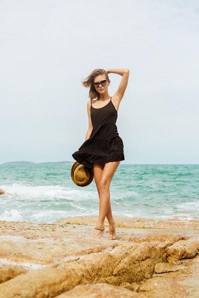 Sexy Brazilian woman standing on the rocks near the ocean
